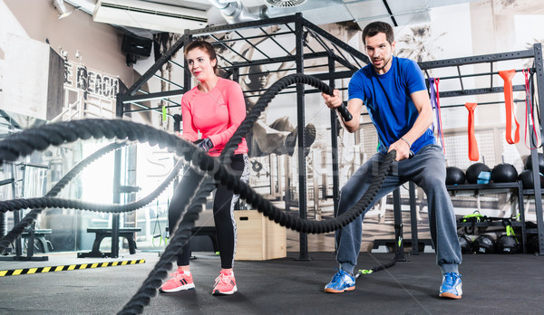 Woman and man in gym functional training with battle rope Stock photo © Kzenon