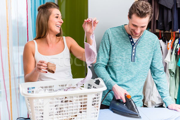 Young couple, woman and man, sharing housework and doing the lau Stock photo © Kzenon