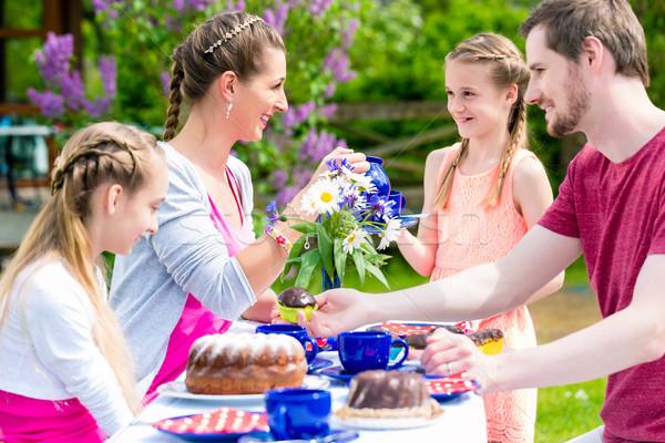 Family having coffee time in garden eating cake Stock photo © Kzenon