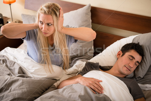 Woman annoyed by the snoring of her partner Stock photo © Kzenon