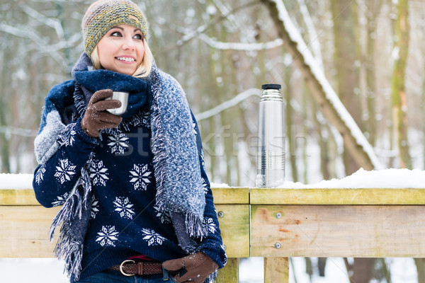 Woman freezing on a cold winter day warming herself up with hot  Stock photo © Kzenon
