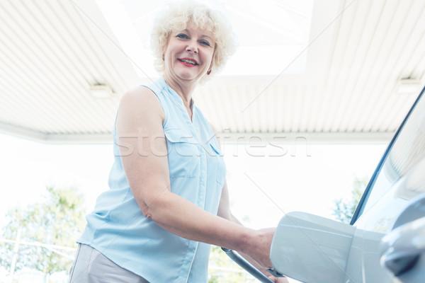 Close-up of the hand of a senior female driver holding the gas dispenser Stock photo © Kzenon