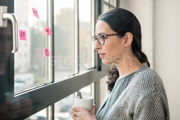 Portrait of young woman day dreaming during break at the office Stock photo © Kzenon
