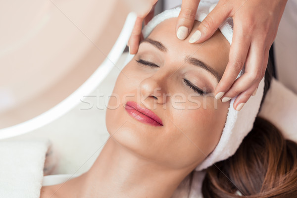 Relaxed woman smiling under the benefits of anti-aging facial massage Stock photo © Kzenon