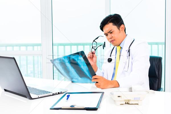 Asian doctor examining x-ray picture in practise Stock photo © Kzenon