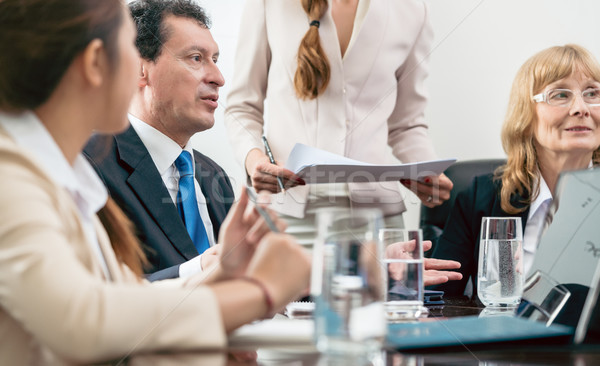 Middle-aged skilled manager cooperating with his colleagues Stock photo © Kzenon