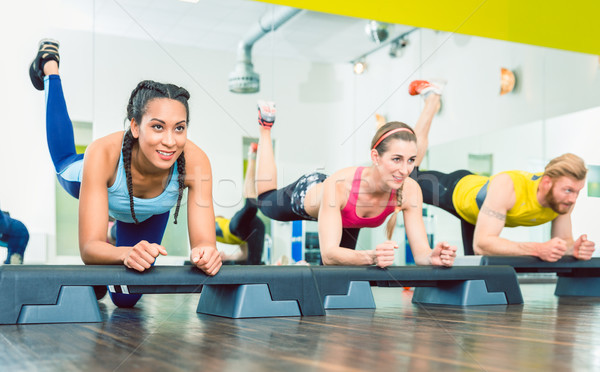 Beautiful young woman exercising a plank variation during group workout Stock photo © Kzenon