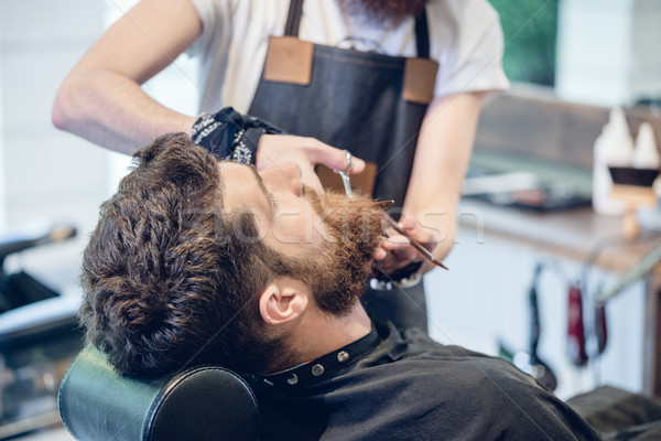 Close-up of the hand of a barber using scissors while trimming Stock photo © Kzenon