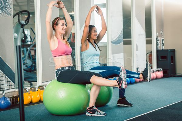 Full length of two fit women sitting on fitness balls while exercising Stock photo © Kzenon