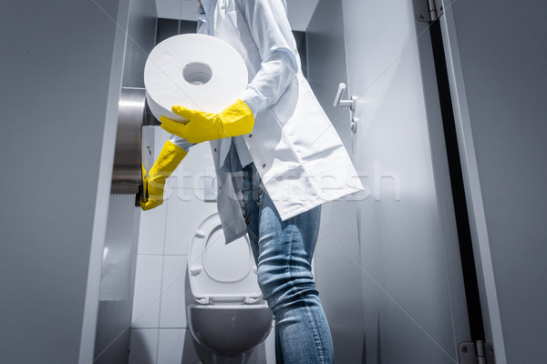 Janitor woman changing paper in public toilet Stock photo © Kzenon