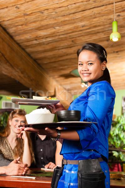 Młodych ludzi kelnerka jedzenie tajska restauracji dania Zdjęcia stock © Kzenon