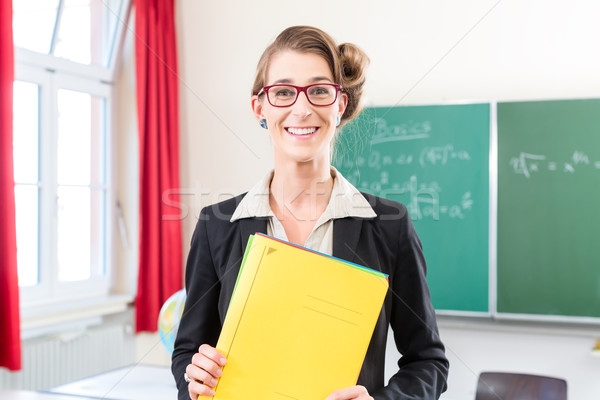 Teacher holding folder in school in front of a class Stock photo © Kzenon