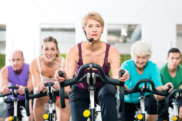 Senior people in gym spinning on fitness bike  Stock photo © Kzenon