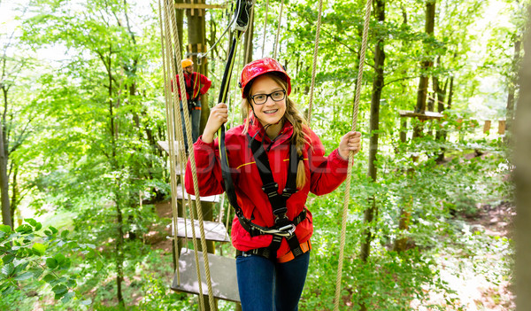 Teenager girl climbing in high rope course or parlor Stock photo © Kzenon