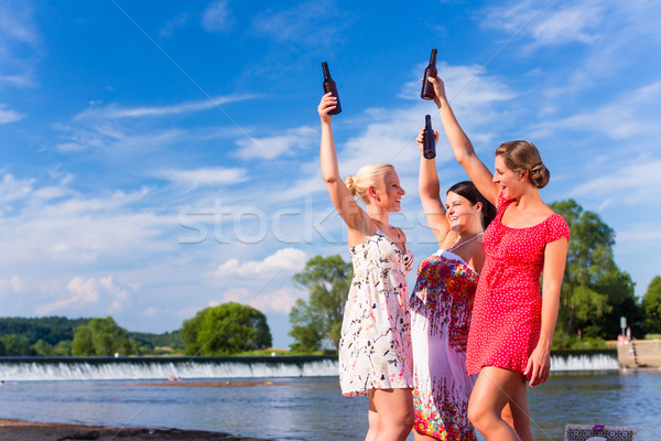 Friends clinking and saying Cheers at river beach Stock photo © Kzenon