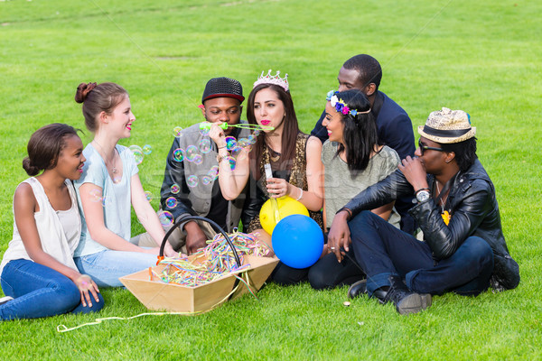 Multicultural group, sitting together on lawn Stock photo © Kzenon