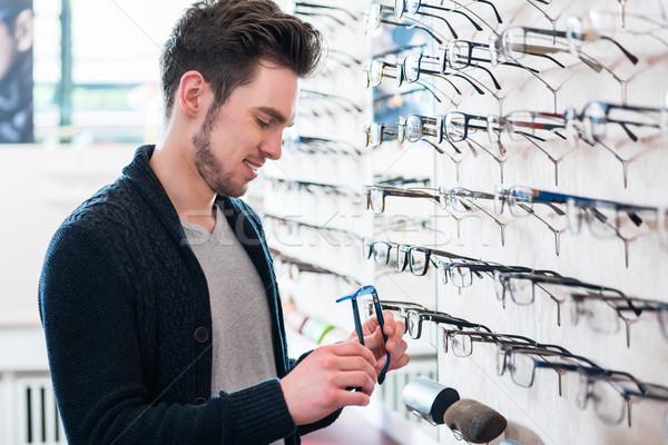 Férfi választ szemüveg polc optikus bolt Stock fotó © Kzenon