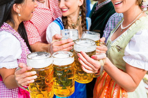 Friends having fun in beer garden while clinking glasses Stock photo © Kzenon