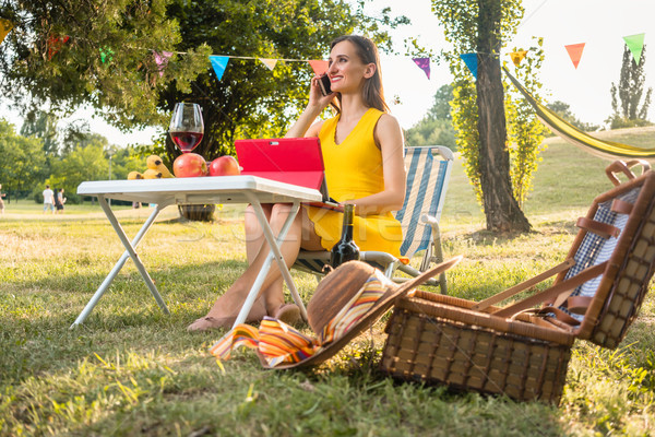 Active young woman talking on mobile and using tablet during pic Stock photo © Kzenon