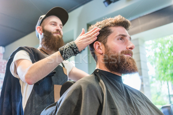 Handsome bearded young man ready for a trendy haircut in a cool  Stock photo © Kzenon