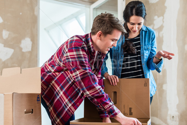 Young couple opening boxes during renovation of new home after m Stock photo © Kzenon