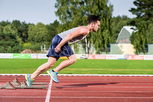 Athlete on cinder track of sports facility starts to sprint Stock photo © Kzenon