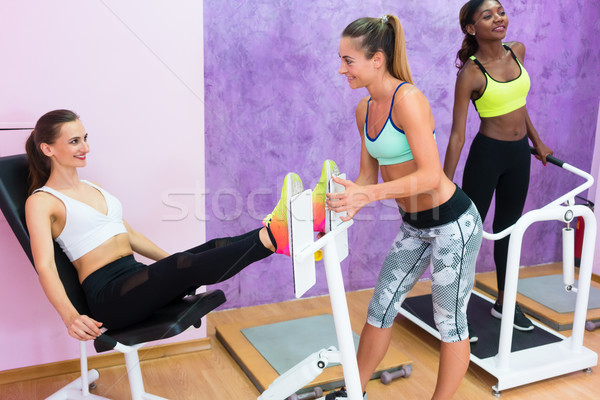 Determined fit women exercising under guidance of experienced fitness instructor Stock photo © Kzenon