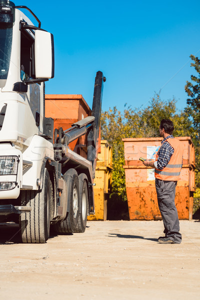 Worker on construction site unloading container for waste from truck Stock photo © Kzenon