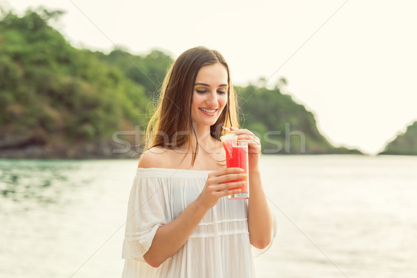 Portrait of a young woman holding a fresh watermelon cocktail on tropical beach Stock photo © Kzenon
