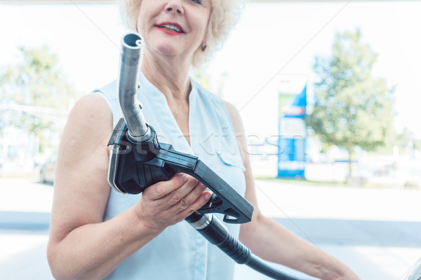 Close-up of the hand of a senior female driver holding the gas dispenser Stock photo © Kzenon