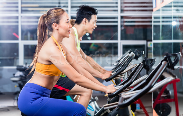 Sportive Asian couple doing indoor cycling in gym  Stock photo © Kzenon