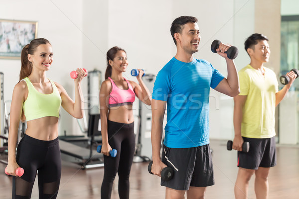 Fit handsome man smiling while exercising bicep curls during group workout Stock photo © Kzenon
