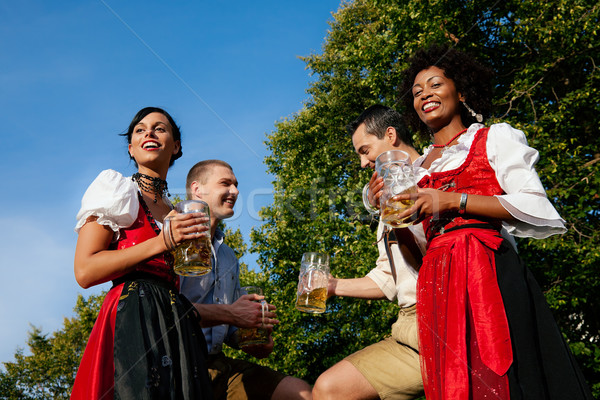 Group of four friends in beer garden Stock photo © Kzenon