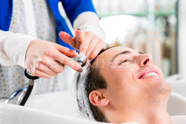 Hairdresser washing man hair in barbershop Stock photo © Kzenon
