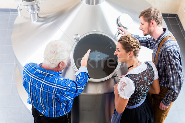 Brewer and couple in beer brewery guided tour Stock photo © Kzenon