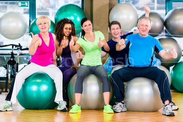 Men and women sitting on fitness balls in gym Stock photo © Kzenon