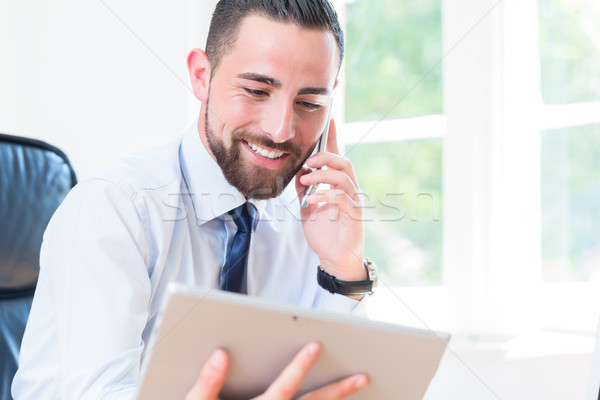 Businessman in office with tablet and phone Stock photo © Kzenon