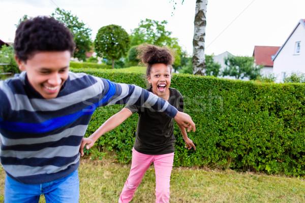 Siblings playing in garden Stock photo © Kzenon