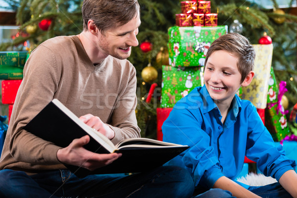 Daddy reading out from book for kid under X-mas tree on Christma Stock photo © Kzenon