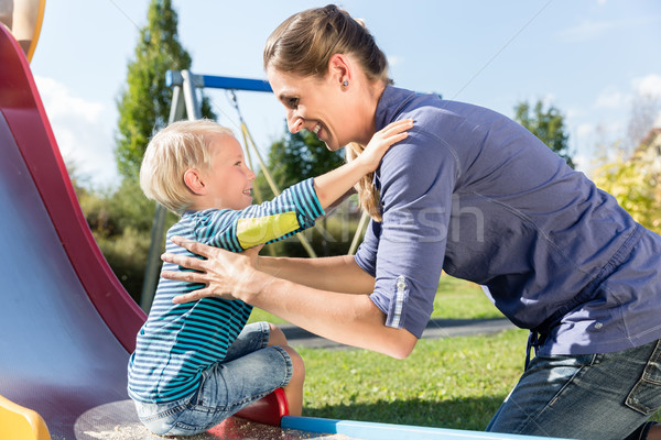 Woman and little boy chuting down slide at playground Stock photo © Kzenon