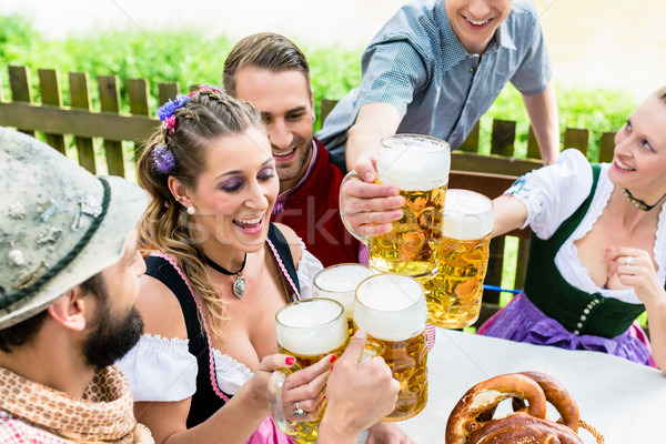 Clinking glasses with beer in Bavarian pub Stock photo © Kzenon