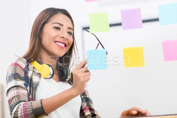 Young employee looking at multiple reminders while planning her  Stock photo © Kzenon