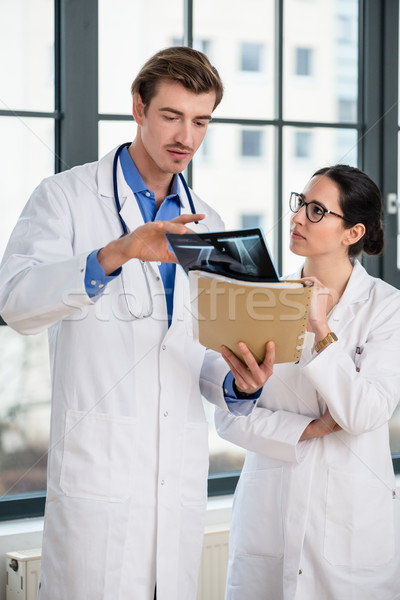 Experienced physician and his colleague interpreting the radiogr Stock photo © Kzenon