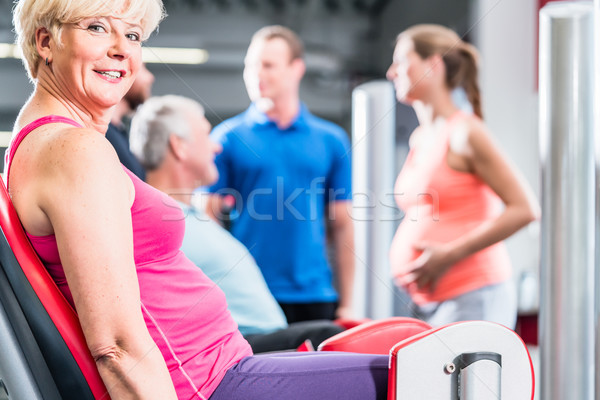 senior woman in group with pregnant woman working out at the gym Stock photo © Kzenon