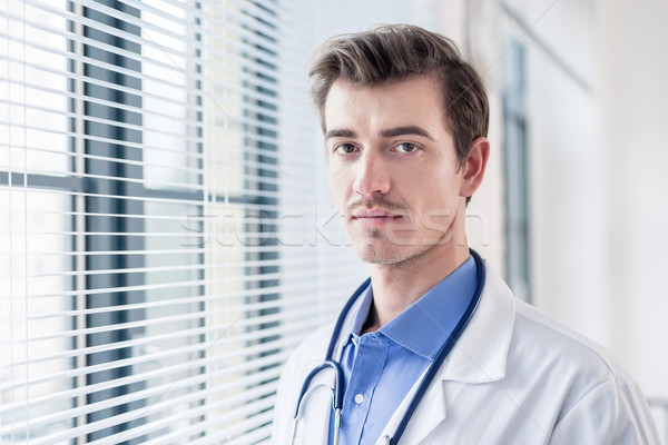Portrait of a young serious doctor looking at camera with determ Stock photo © Kzenon