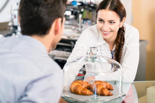 дружественный официантка указывая французский круассаны кофе Сток-фото © Kzenon