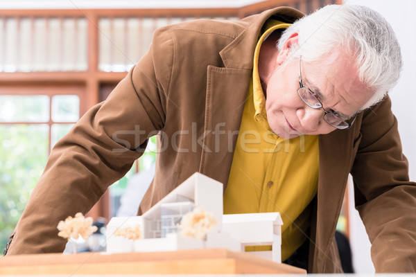 Senior architect working on the project of a modern building Stock photo © Kzenon