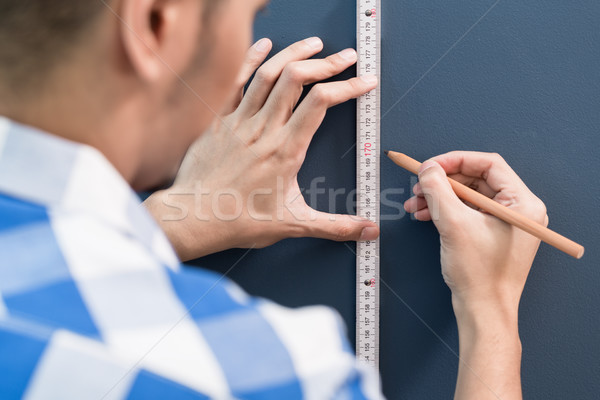Stock photo: Young handyman sizing with yardstick and pencil