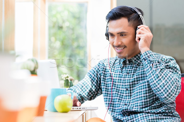 Young Asian man listening and watching an online video Stock photo © Kzenon