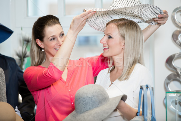 Girlfriends on shopping spree trying ladies hats and other fashion Stock photo © Kzenon